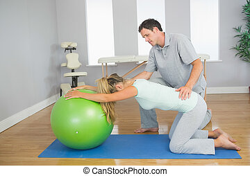 Physiotherapist controlling patient doing exercise with...