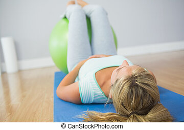 Blonde woman doing exercise with exercise ball on the floor...