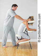 Masseur treating shoulders of client in massage chair in...
