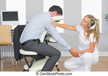 Masseuse treating clients arm in massage chair in bright...
