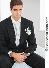 Young handsome bridegroom sitting on bed waiting for the...