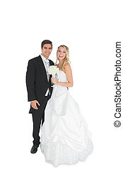 Cheerful young married couple posing smiling at camera on...