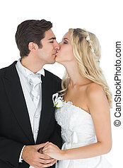 Young married couple posing kissing each other while holding...