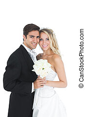 Sweet married couple posing holding a white bouquet on white...