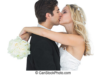 Nice bride embracing and kissing her husband holding a white...