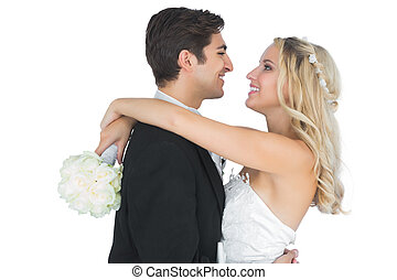 Cheerful pretty bride hugging her husband holding a bouquet