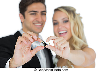 Cheerful married couple showing their wedding rings on white...