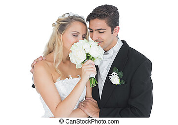 Young married couple posing having a sniff of the bouquet on...