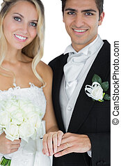 Young married couple posing wearing wedding rings smiling at...