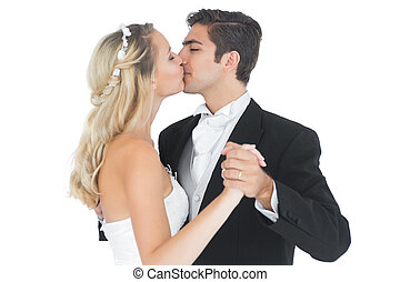Young married couple dancing viennese waltz kissing each...