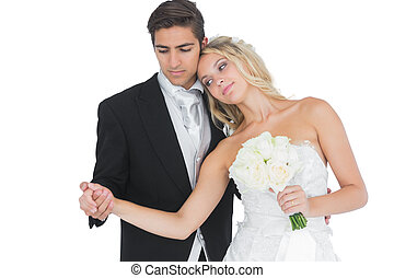 Young beautiful bride posing with her husband holding a...