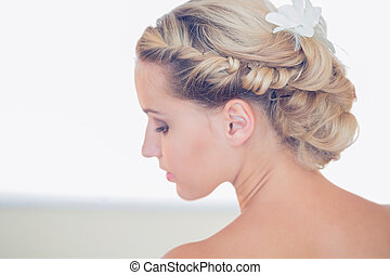 Pretty young bride looking down having a chic coiffure