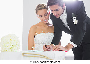 Handsome bridegroom signing wedding contract at desk