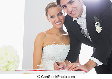 Happy bridegroom signing wedding contract smiling at camera