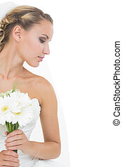 Attractive blonde bride holding a bouquet looking down on...