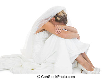 Unhappy blonde bride sitting on floor hiding her face