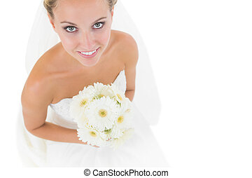 Smiling blonde bride looking up at the camera holding a...