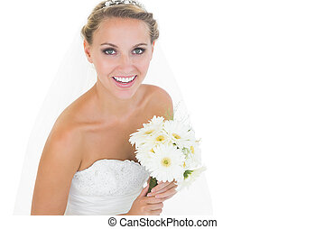 Side view of cheerful young bride holding a bouquet smiling...