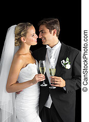 Gorgeous young married couple posing holding champagne...