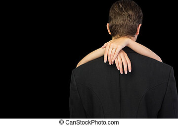 Rear view of young man being hugged by his wife on black...
