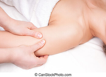 Therapist doing a pressure point massage of deltoid muscle on a woman's right shoulder