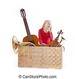young girl with musical instruments in box against white...