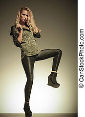 woman in leather pants kicking and posing