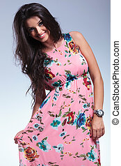 young smiling woman pulling her pink floral dress