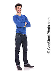 full body picture of a young confident man with arms folded...