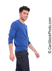 side view of a young walking smiling man