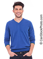 young casual man with hands in pockets smiling