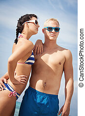 attractive young couple in swimwear and sunglasses