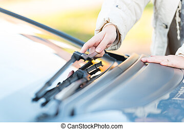 Hand picking up windscreen wiper - Woman's hand picking up...