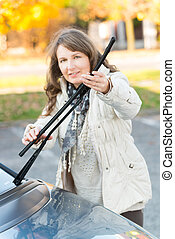 Woman picking up windscreen wiper - Beautiful woman picking...