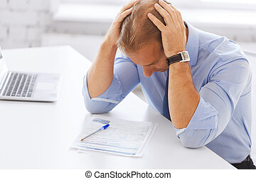 stressed businessman with papers at work - business, office,...
