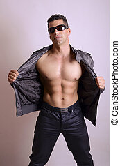 Sexy stripper - Sexy man with sunglasses show abs in studio...
