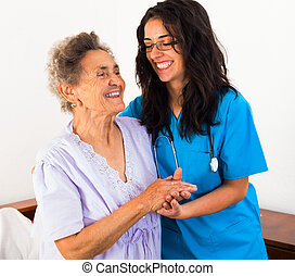 Nurses Caring for Elderly Patients - Happy nurses keeping...