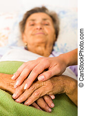 Caring Nurse Holding Hands - Health care nurse holding...