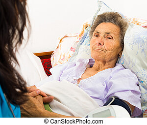 Caring for Senior Patient - Nurse using digital blood...