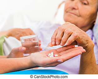Daily Medicine from Nurse - Homecare nurse helping elderly...