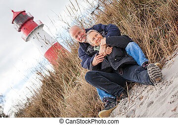 happy mature couple relaxing baltic sea dunes in autumn