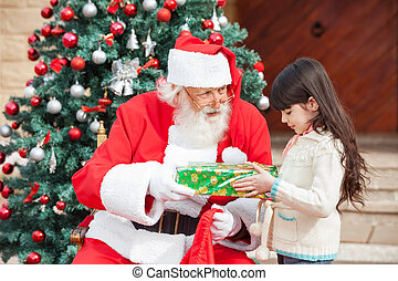 Girl Taking Gift From Santa Claus - Side view of girl taking...