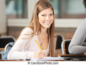 College Student Sitting At Desk In Classroom