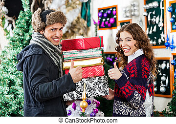 Couple Gesturing Thumbs Up While Holding Christmas Presents...