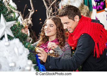 Couple Shopping For Christmas Tree - Happy young couple...