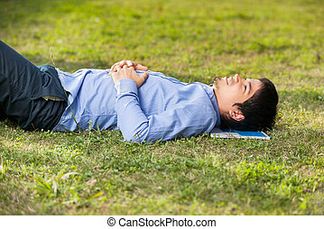 Student Relaxing On Grass At University Campus - Side view...