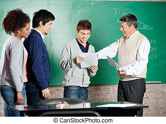 Professor Giving Exam Result To Student At Classroom - Happy...