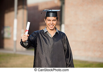Confident Student Showing Diploma On Graduation Day At Campus