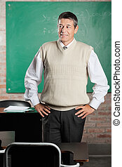 Teacher With Hands On Hips Looking Away In Classroom -...