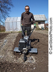 Garden cultivator - Middle aged man working in the garden...